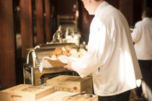 Kelner podający bułeczki na bufet dla gości hotelowych.