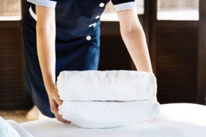 Pokojowa kładąca ręczniki na łóżko dla gości hotelowych.
